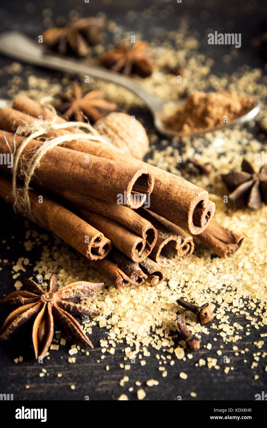 Christmas spices and baking ingredients. Cinnamon sticks, anise stars, nutmeg, cardamom, cloves, brown sugar and - Stock Image