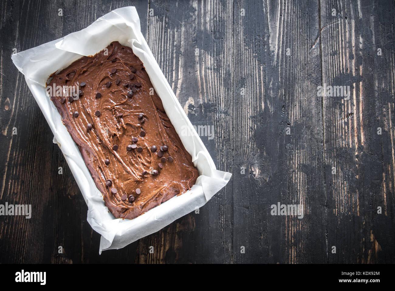 Basic homemade brownie or chocolate cake raw dough in baking pan. Cooking (baking) homemade chocolate cake or brownie. - Stock Image