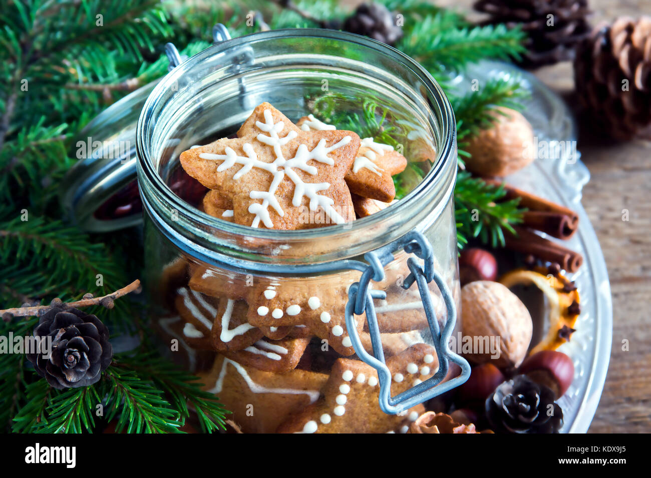 Gingerbread Christmas cookies stars in the glass jar with fir branches, Christmas spices and decor close up Stock Photo