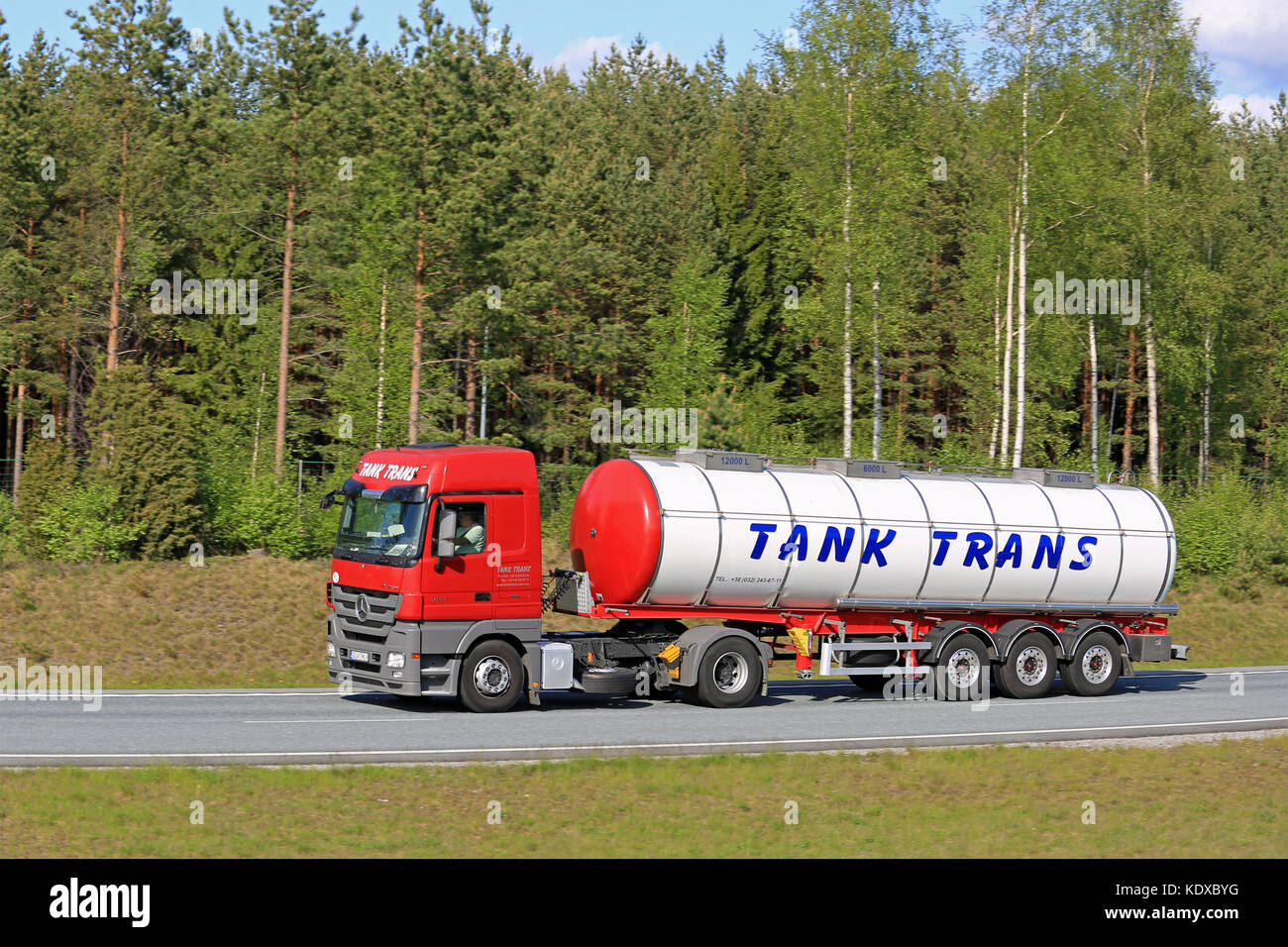 SALO, FINLAND - MAY 22, 2016: Red Mercedes-Benz Actros semi tank truck drives along motorway flanked by forest in - Stock Image