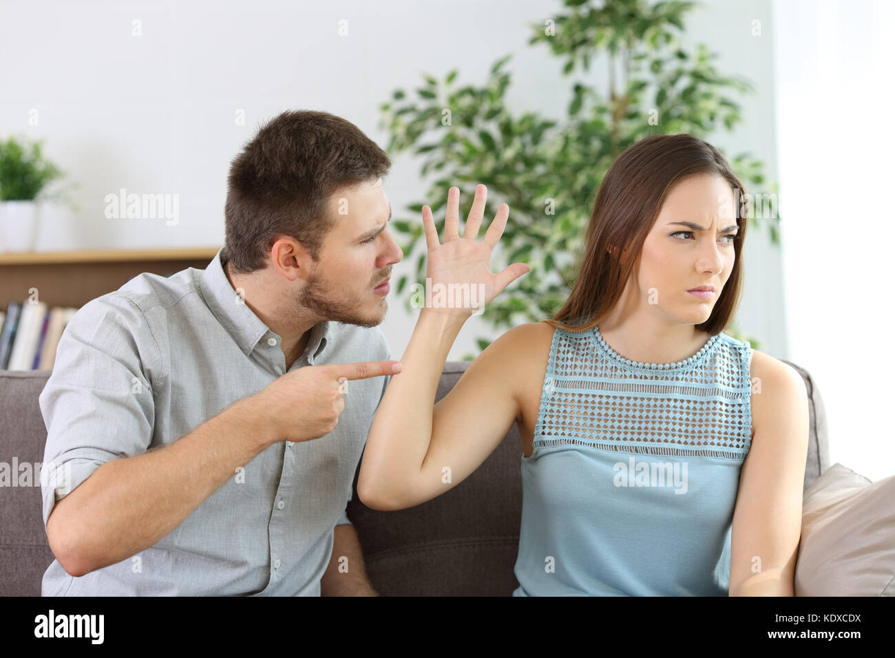 Angry couple fighting sitting on a couch at home - Stock Image