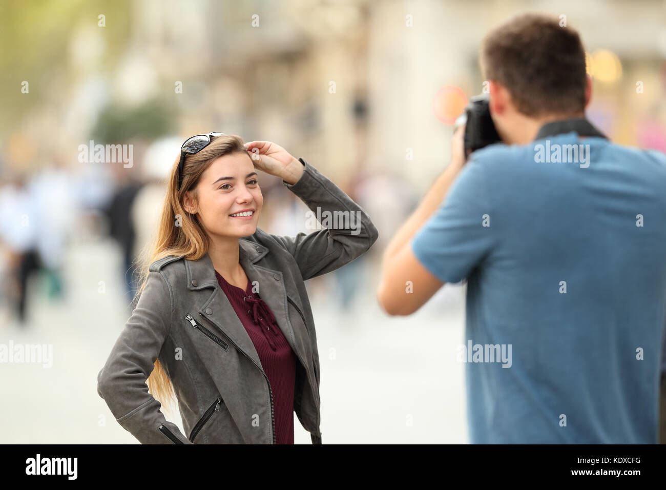 Photographer photographing to a fashion model on the street - Stock Image