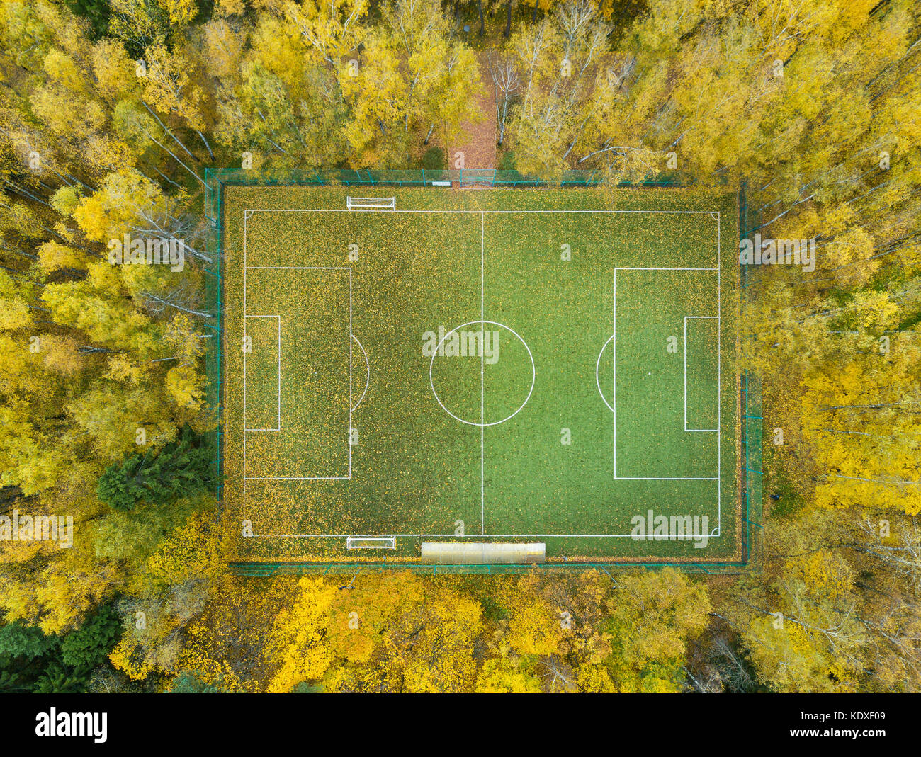 Football pitch surrounded by autumn yellow forest - aerial view - Stock Image