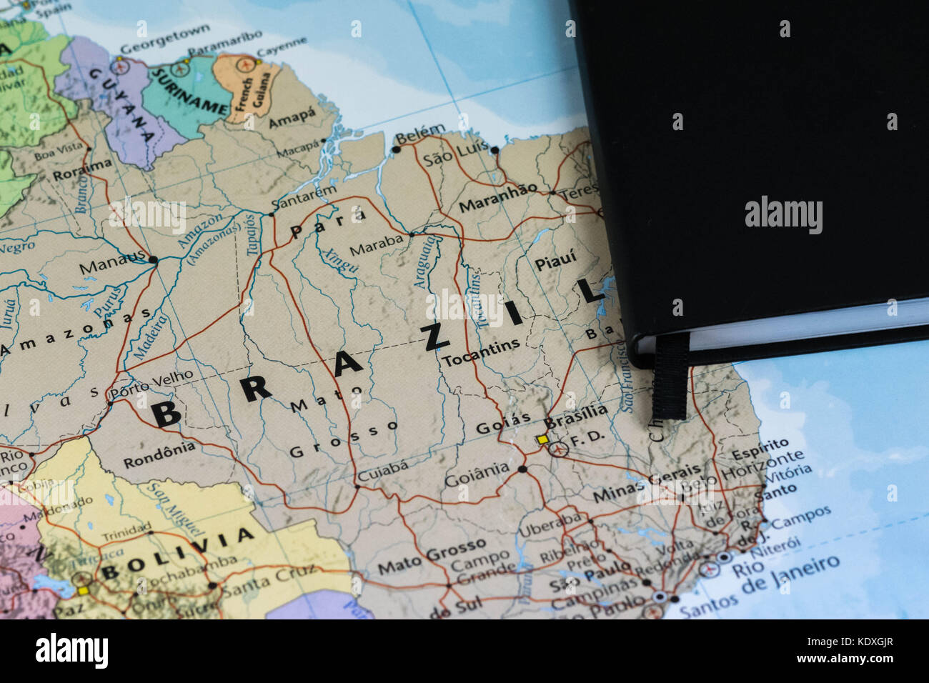 personal lanning notes of a traveller planning a trip to Brazil over a closeup map of Brazil - Stock Image