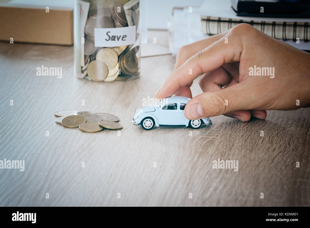 Car in men hand on desk with blured money coin in jar bank saving Concept for maintenance costs and taxes car,warm Stock Photo