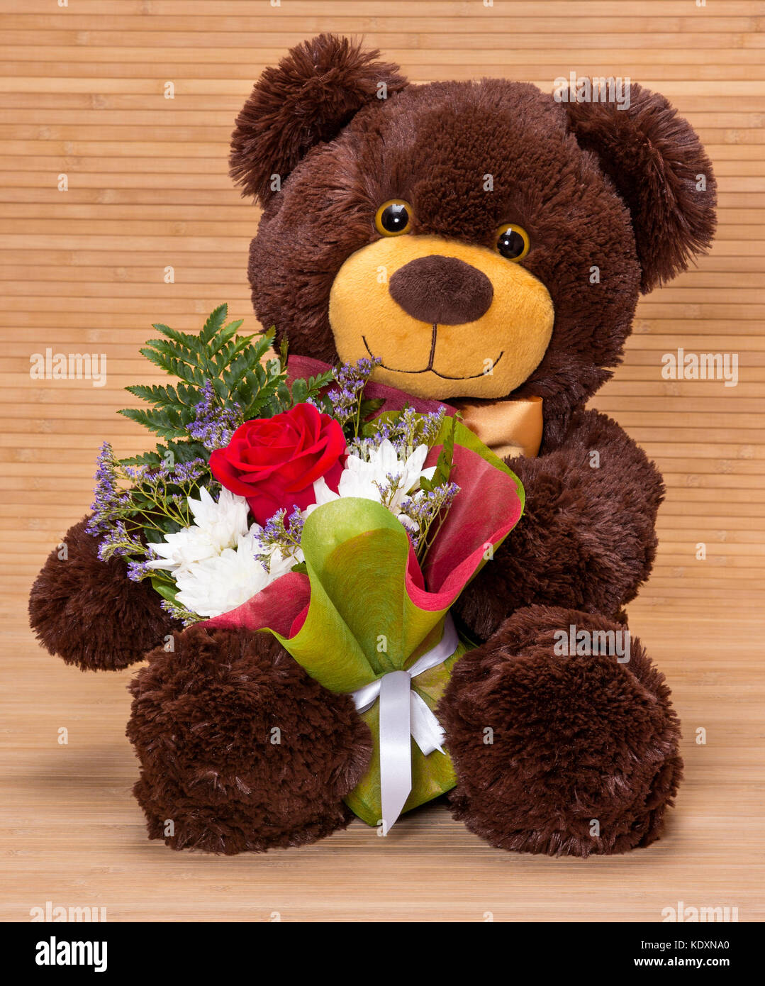 Smiling teddy bear holding beautiful floral bouquet in paws - Stock Image
