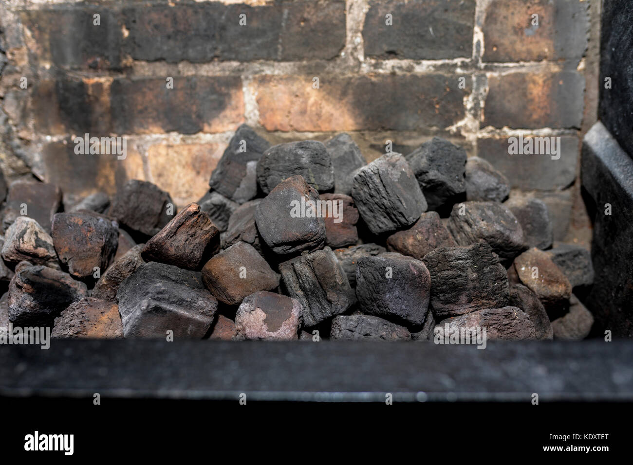 Coal in an unlit kitchen fireplace with no fire - Stock Image