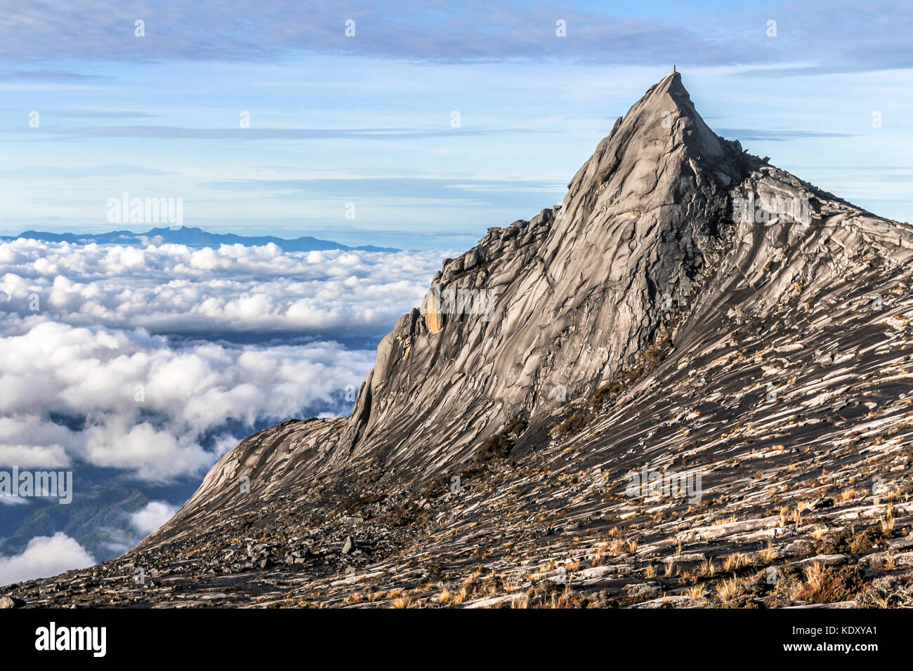 Peak of Mount Kinabalu and clouds below in the morning hours, Kota Kinabalu national park Borneo, Malaysia - Stock Image