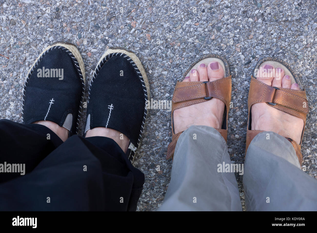 Casual summer footwear choices:  women's closed-toe shoes (espadrilles) and open-toe sandals. - Stock Image