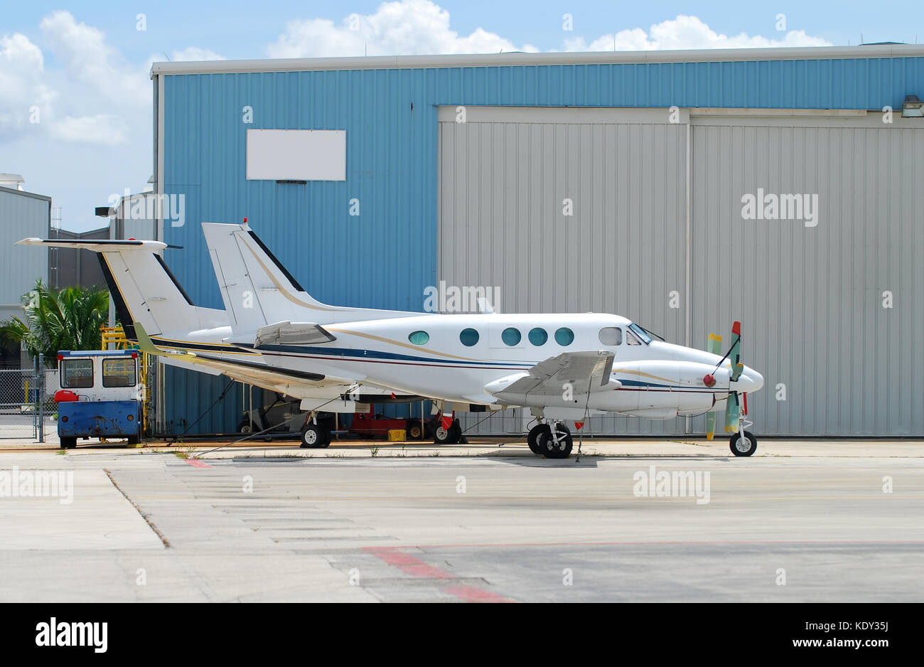 Two turboprop airplanes parked in front of hangar - Stock Image