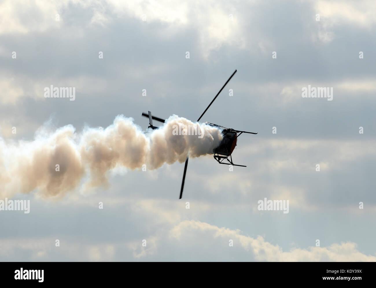 Light helicopter with smoke making emergency landing - Stock Image