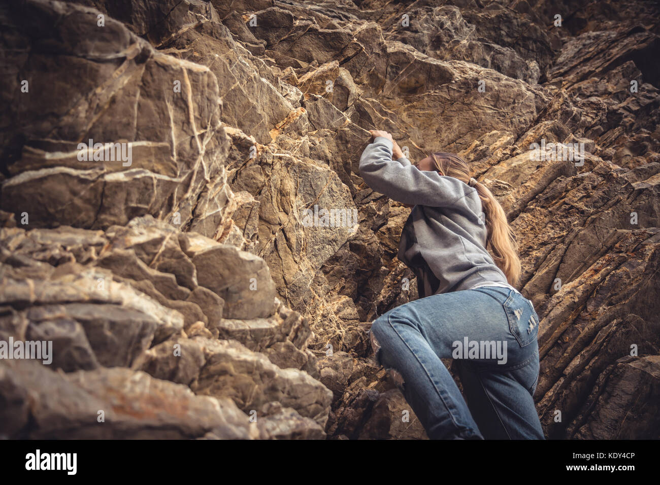 Courage woman achieving her goal climbing up on rock - Stock Image