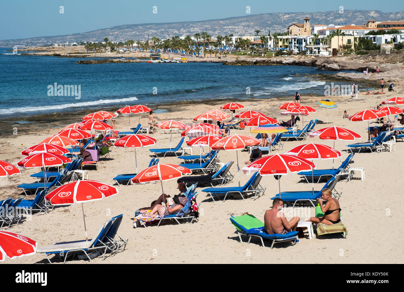 Holidaymakers bask in the sun on the Paphos Municipal beach in Kath Paphos, Cyprus. - Stock Image