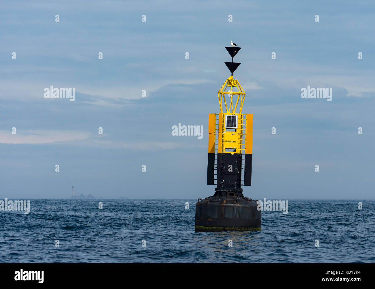 The Runnel Stone South Cardinal marker buoy with Longships lighthouse in the background on a calm day - Stock Image