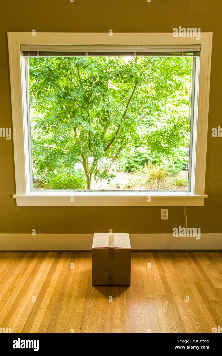 A small cardboard box below a large window in a residential home. - Stock Image
