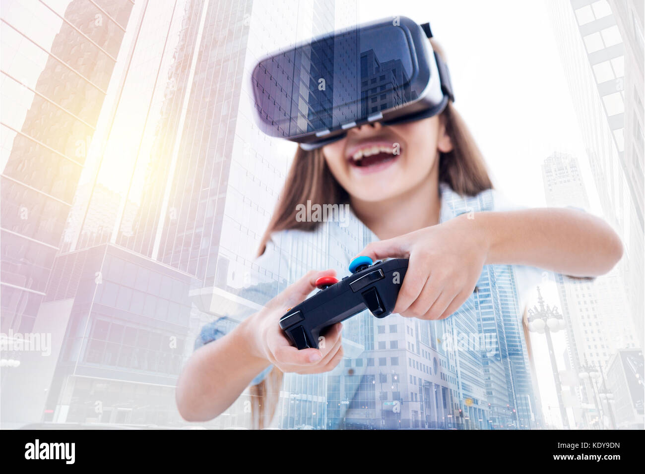 Happy girl in VR headset using video game controller - Stock Image