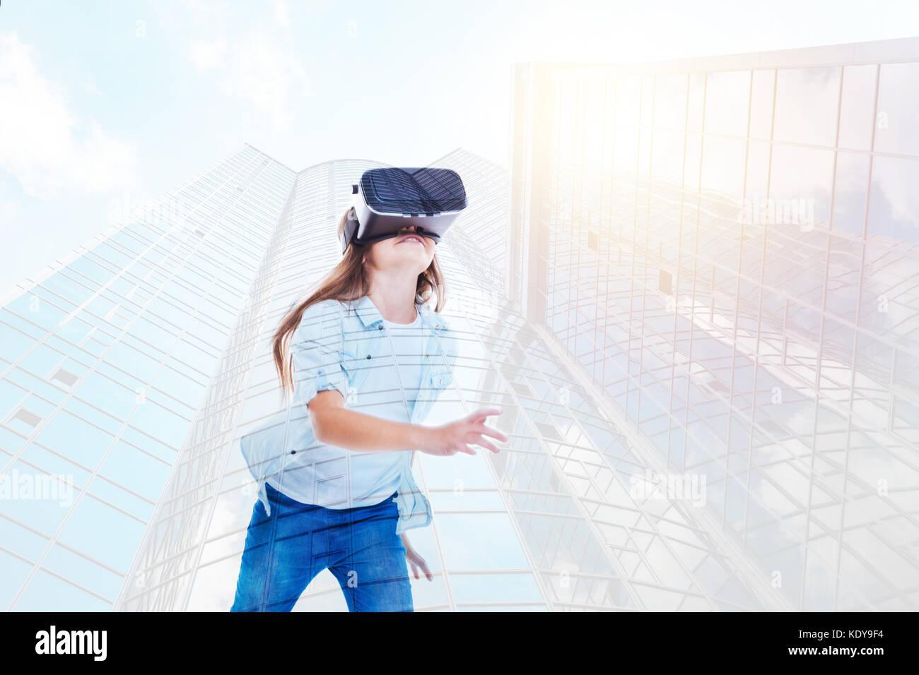 Pre-teen girl running in VR headset - Stock Image