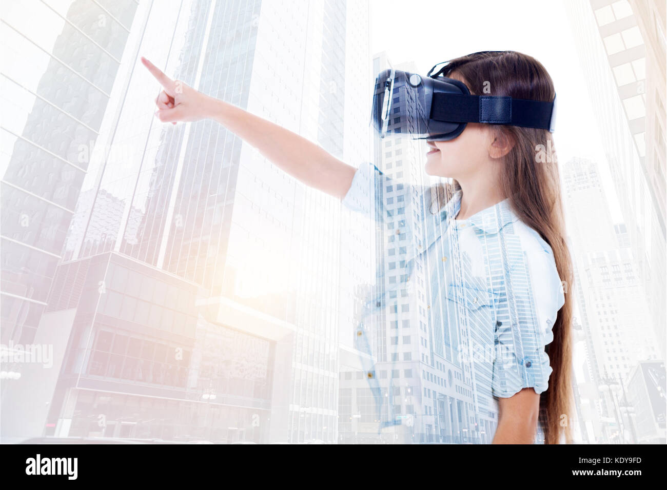 Pre-teen girl in VR headset pointing leftwards - Stock Image