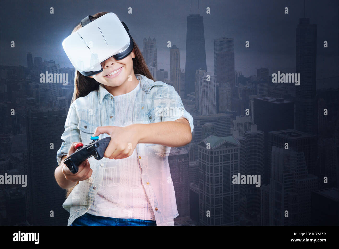 Upbeat girl playing VR game with controller - Stock Image