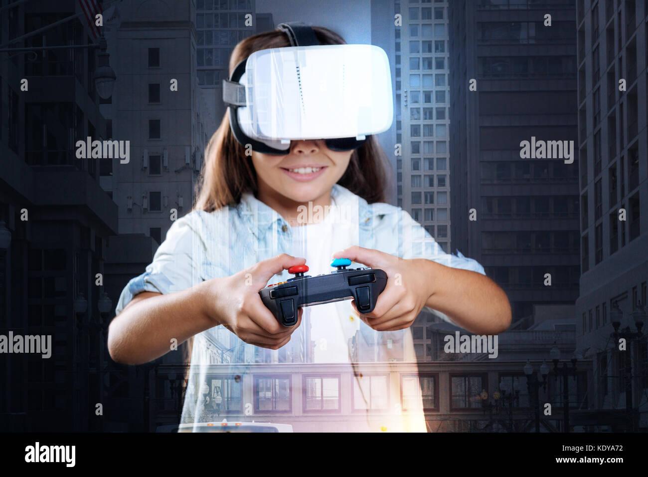 Smiling girl enjoying VR game with controller - Stock Image