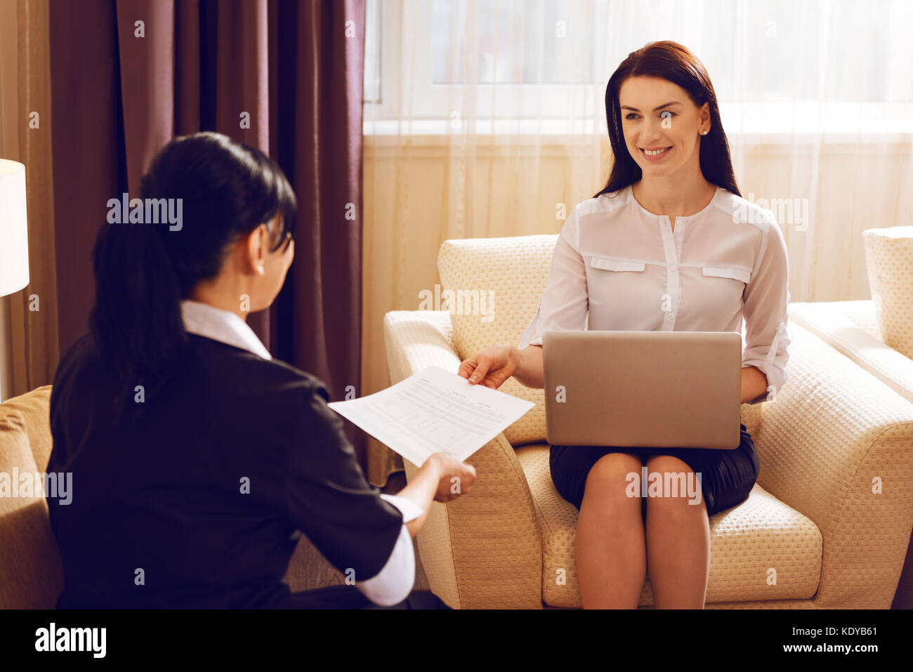 Cheerful female giving document to her helper - Stock Image