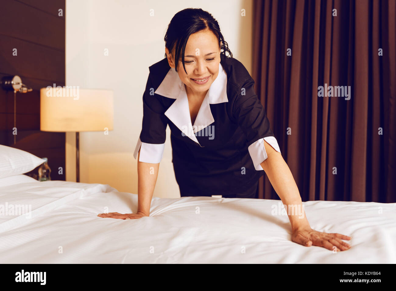 Attentive foreign hotel staff making bed - Stock Image