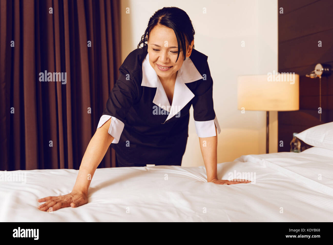 Positive delighted chambermaid doing her job - Stock Image