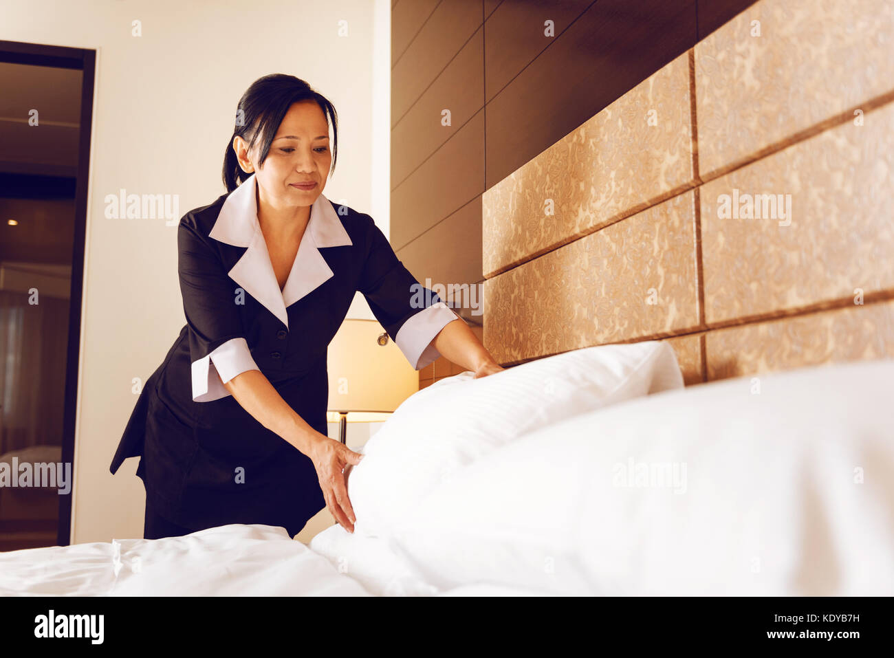 Serious maid putting pillow straight - Stock Image