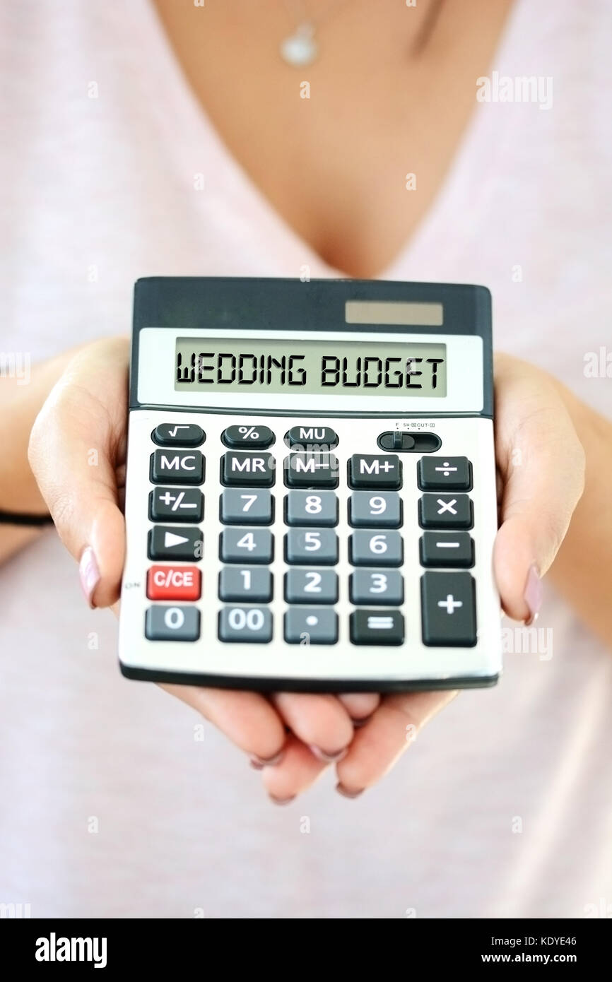 Wedding Budget Calculators | Wedding Cost Concept With Small Calculator In Woman Hand Spelling
