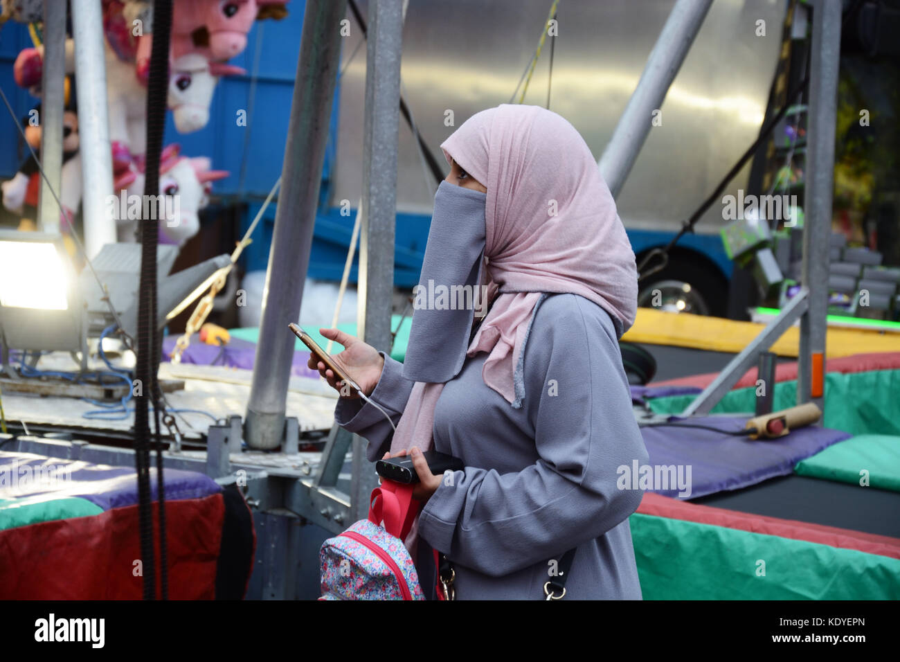 Muslim woman, in Niqab at Fair ground - Stock Image