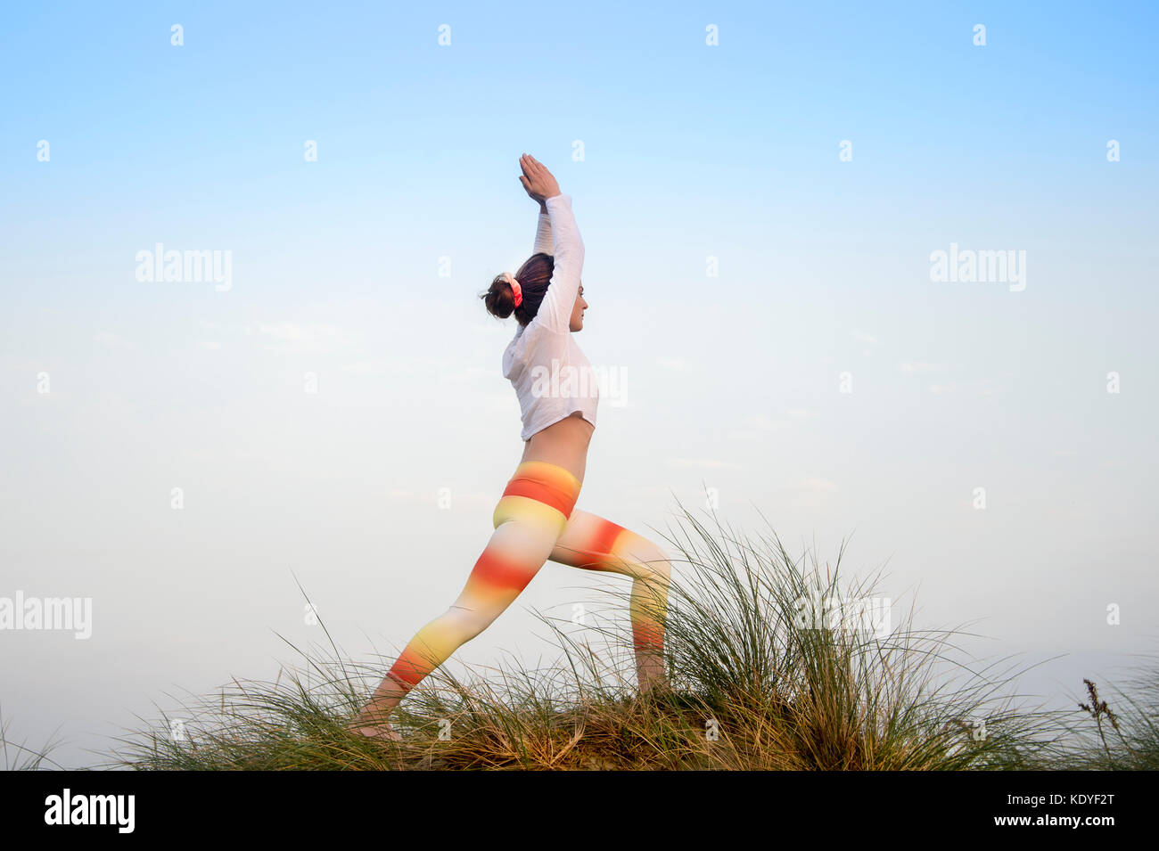 woman wearing sportswear practicing yoga doing a warrior pose in the sand dunes - Stock Image