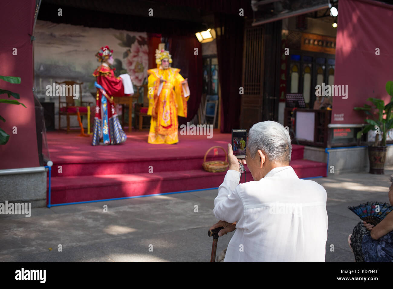 guangzhou,china - Aug,16,2017: Old man watching contonese opera show with moblie. Stock Photo