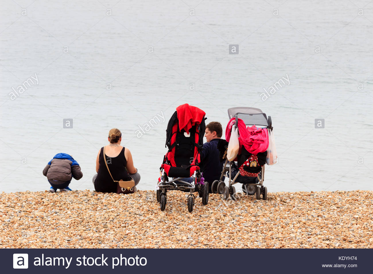 Family enjoying sitting on the shingle beach at Lyme Regis, Dorset, despite overcast, gloomy conditions - Stock Image