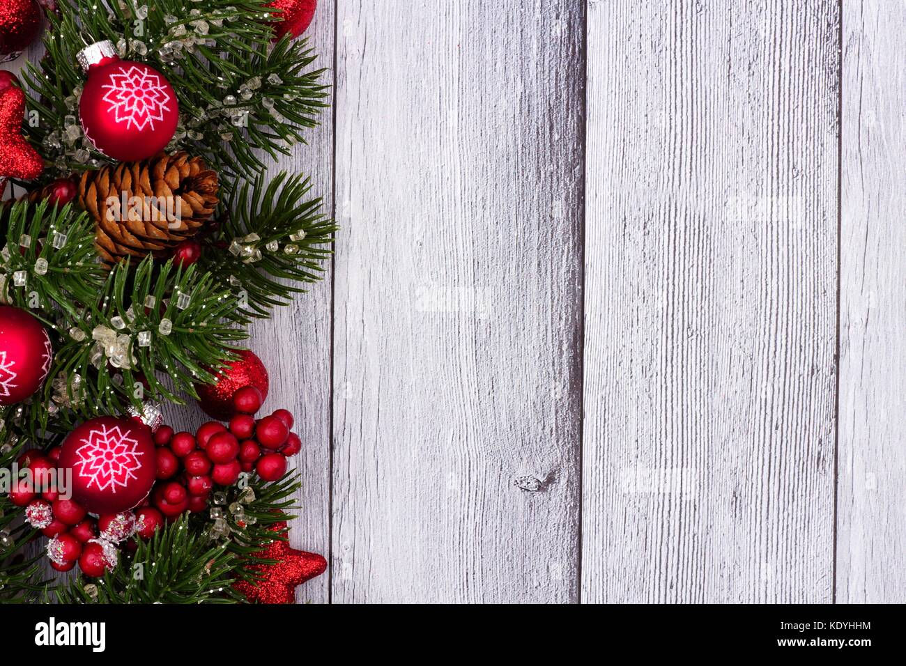 Red Christmas Ornaments And Branches Side Border On A Rustic White Wood Background