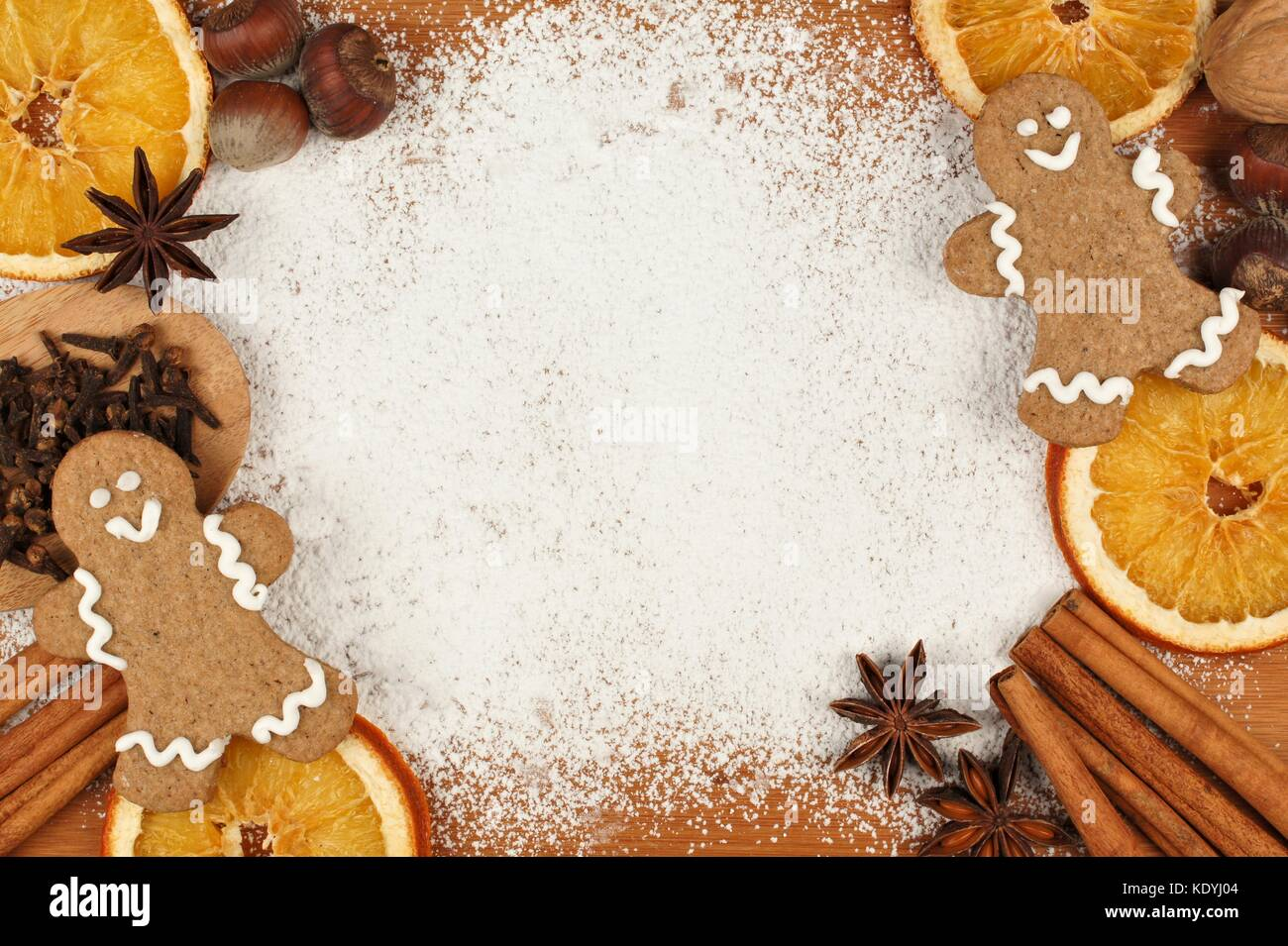 Holiday baking themed frame with gingerbread men, nuts and spices against a powdered sugar background - Stock Image