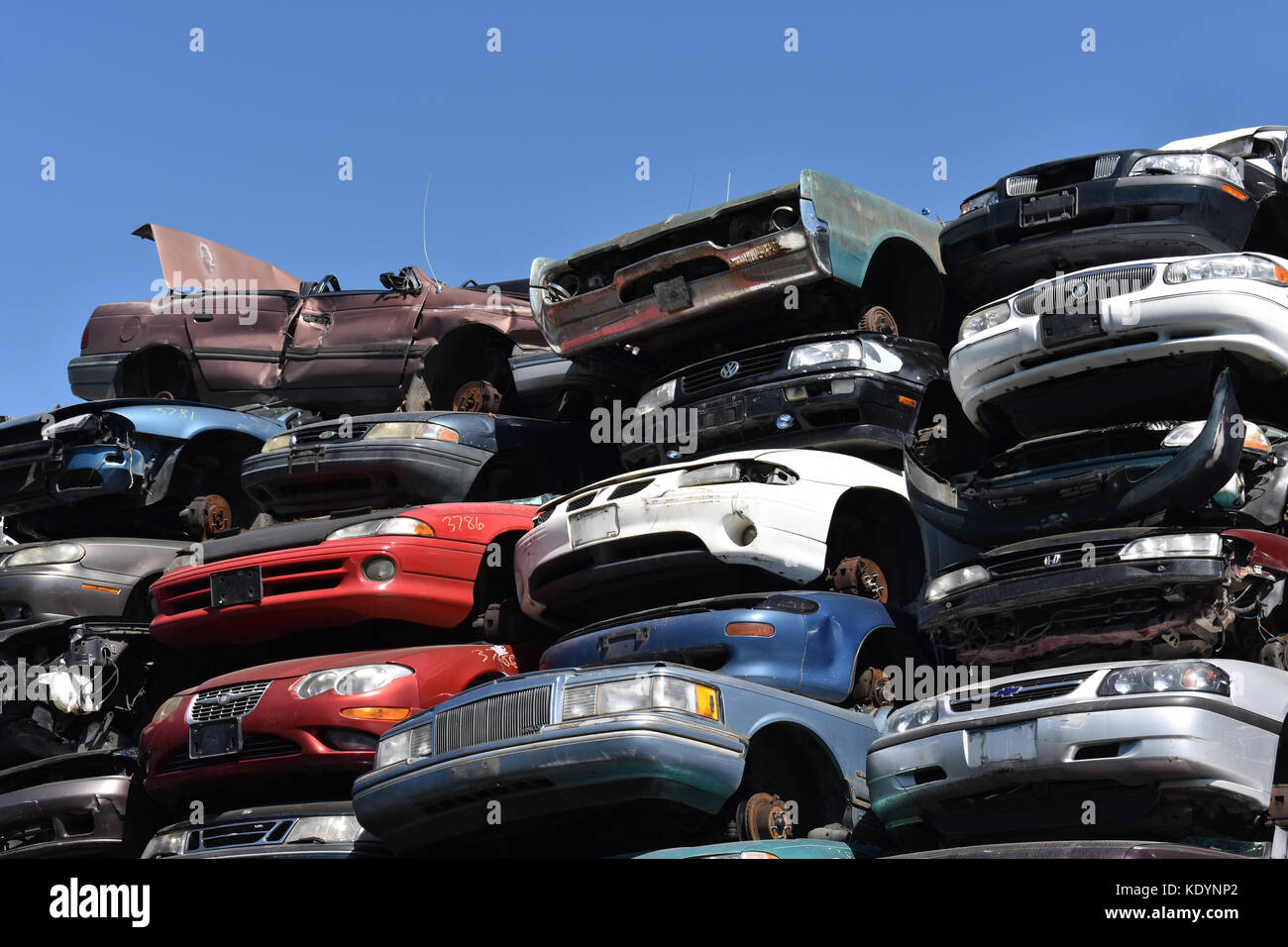 Cars piled high at a junk yard with many cars that are crushed and damaged. - Stock Image