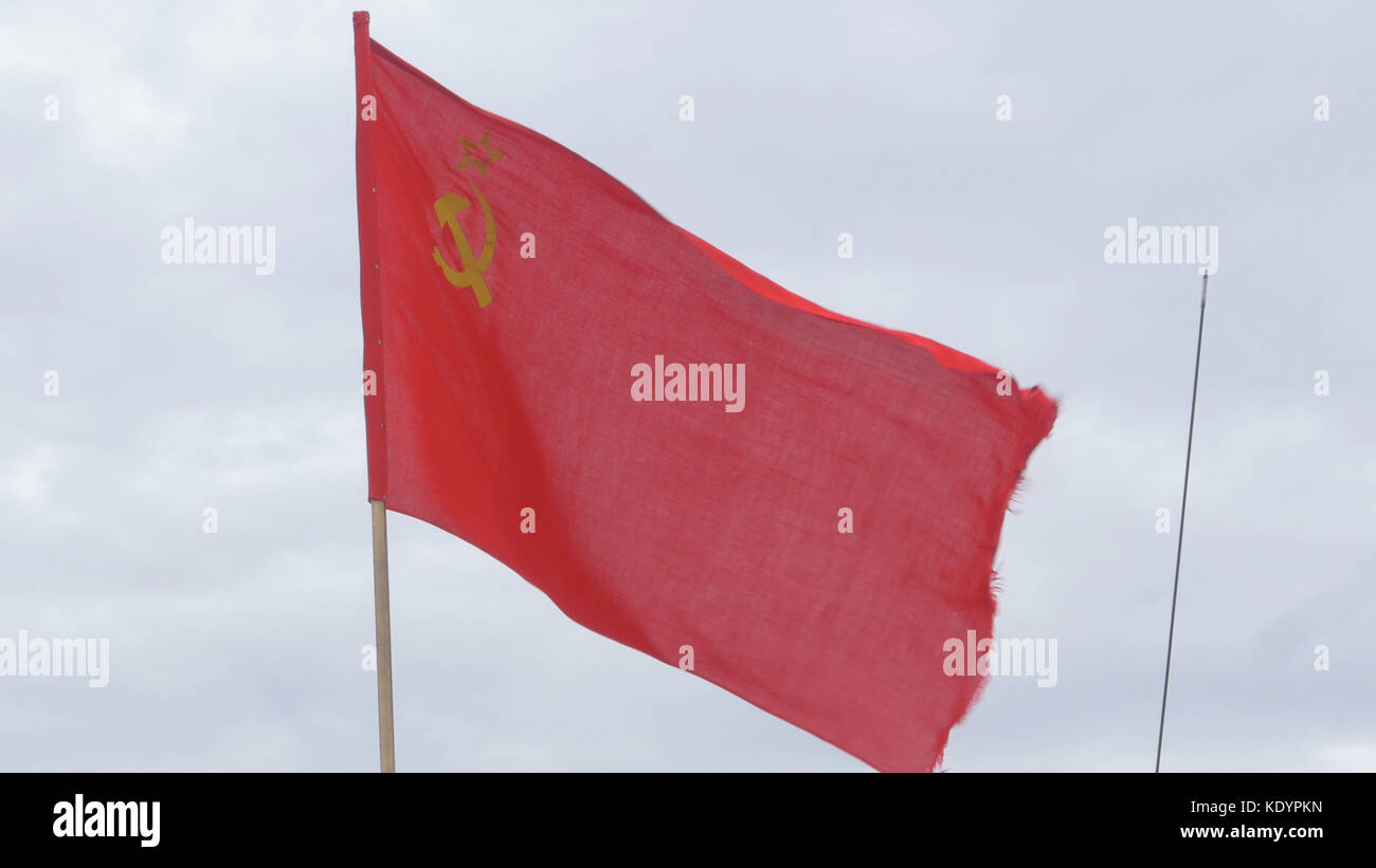 The flag of the USSR developing in the wind on a flagpole in a windy day. Flag of the Soviet Union against the sky - Stock Image