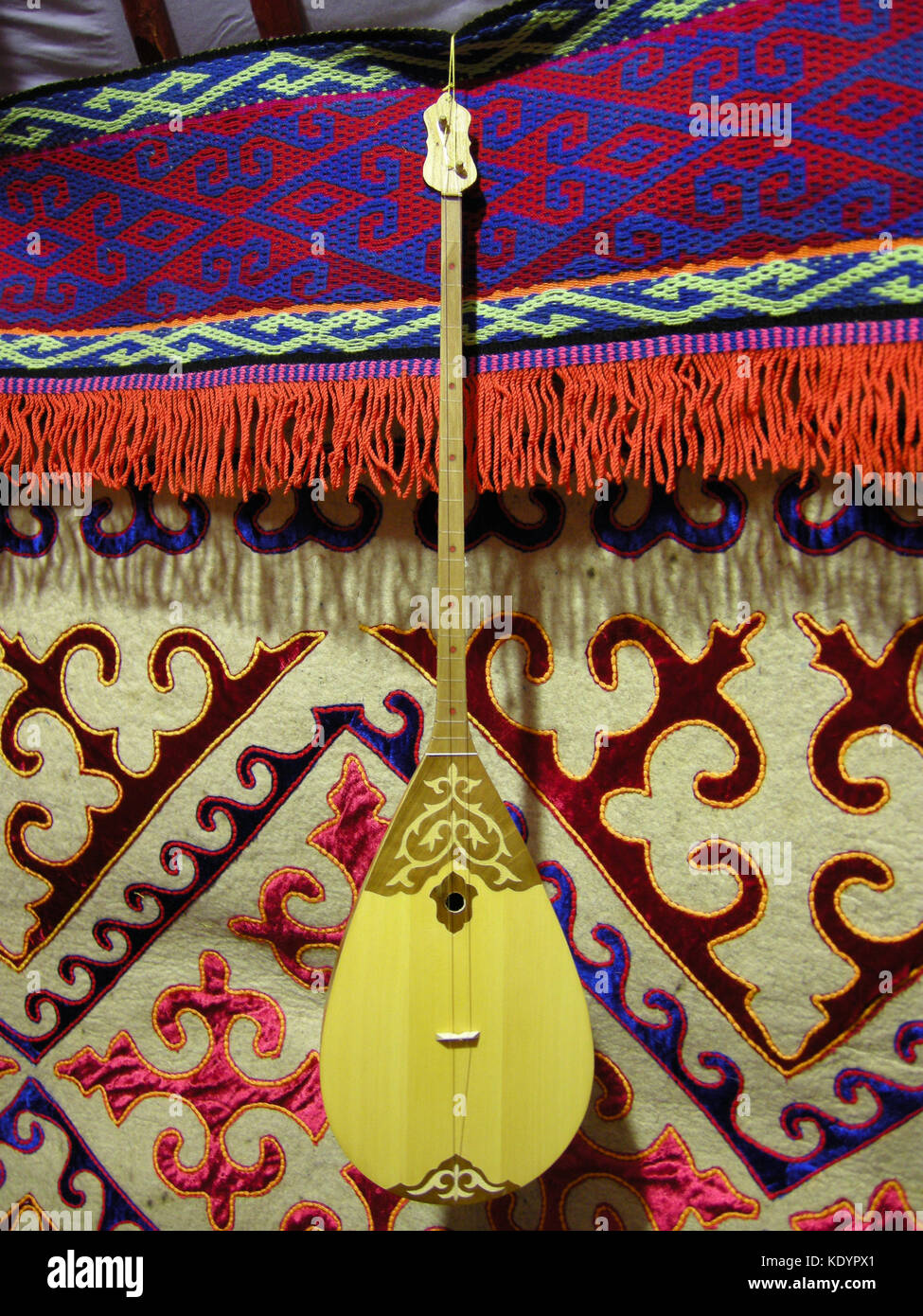 A two-stringed guitar like instrument on display at an exhibit in the Kazakhstan Embassy, Abu Dhabi, UAE - Stock Image