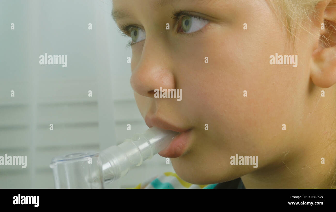 Girl breathing through a steam nebulizer. Treatment bronchopulmonary diseases. Teenager girl with inhaler holds - Stock Image