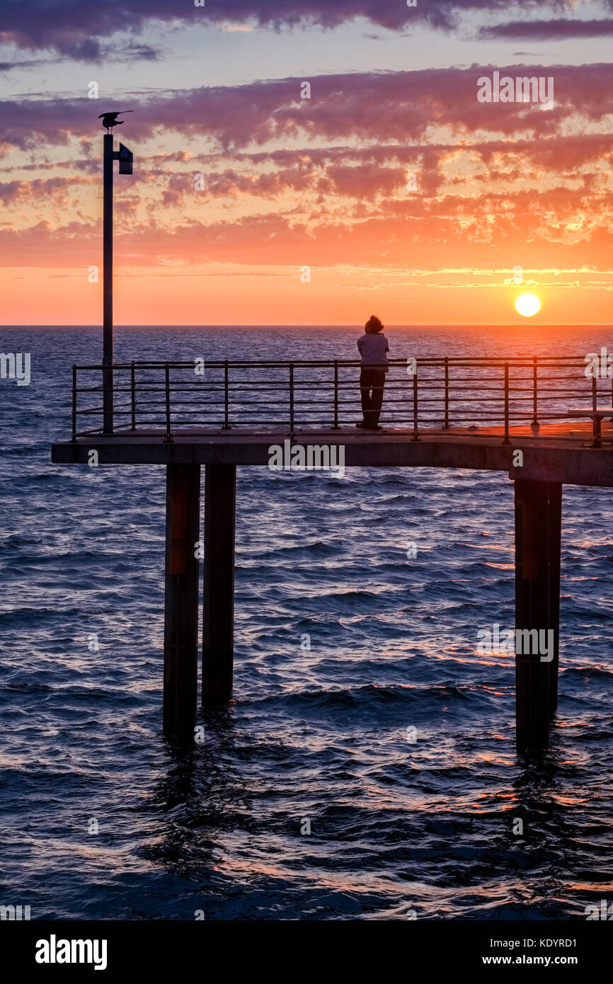 A lone person enjoys a gorgeous sunset at the seaside on Adelaide's Brighton jetty on a balmy summer evening. - Stock Image