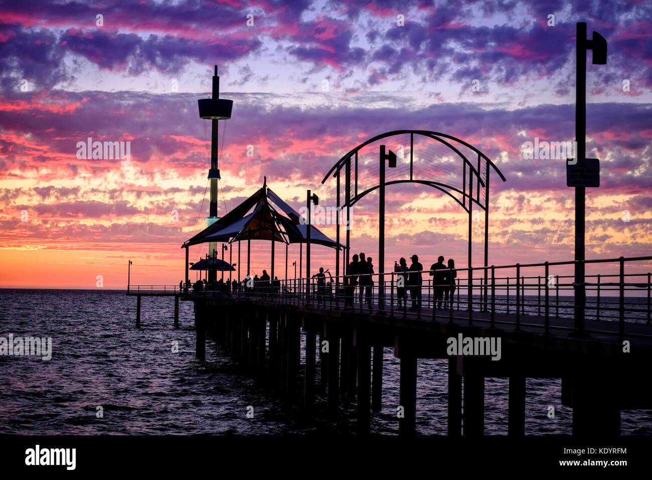 People enjoy a gorgeous sunset at the seaside on Adelaide's Brighton jetty on a balmy summer evening. - Stock Image