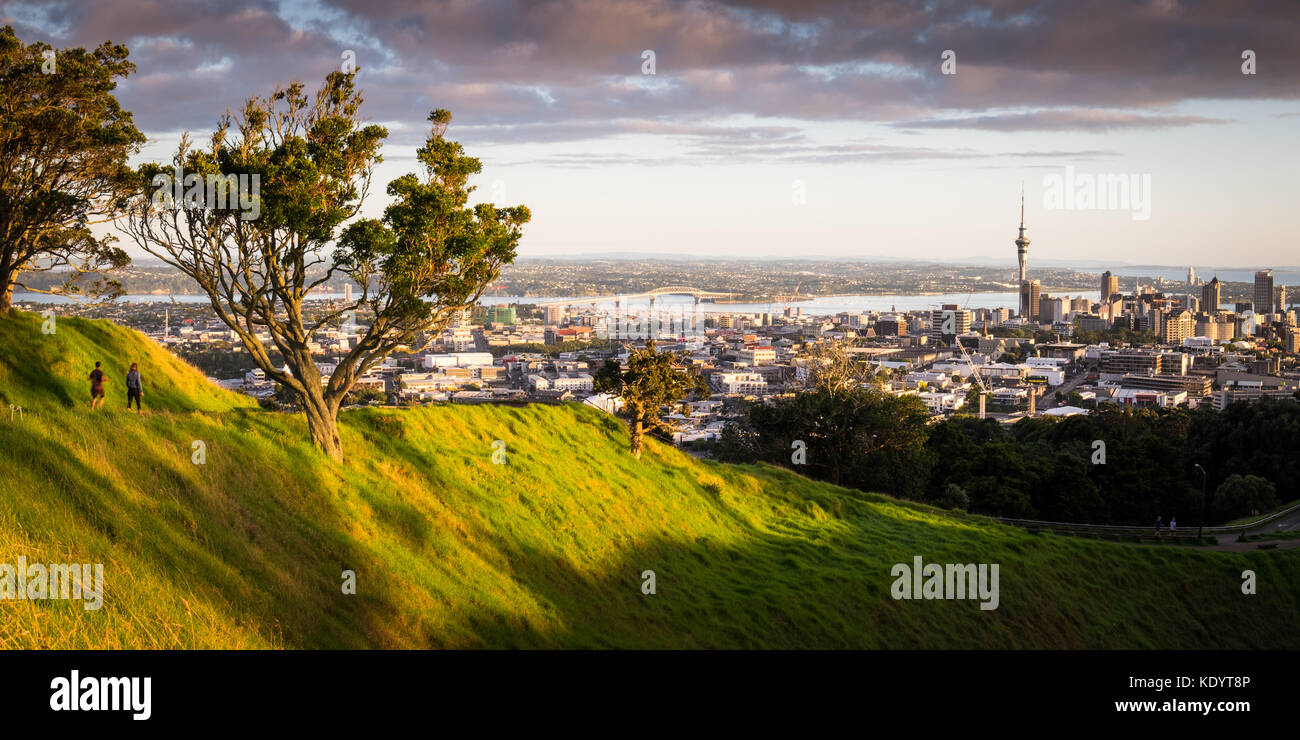 Two people enjoying the Auckland skyline during a morning jog on Mt Eden, New Zealand - Stock Image