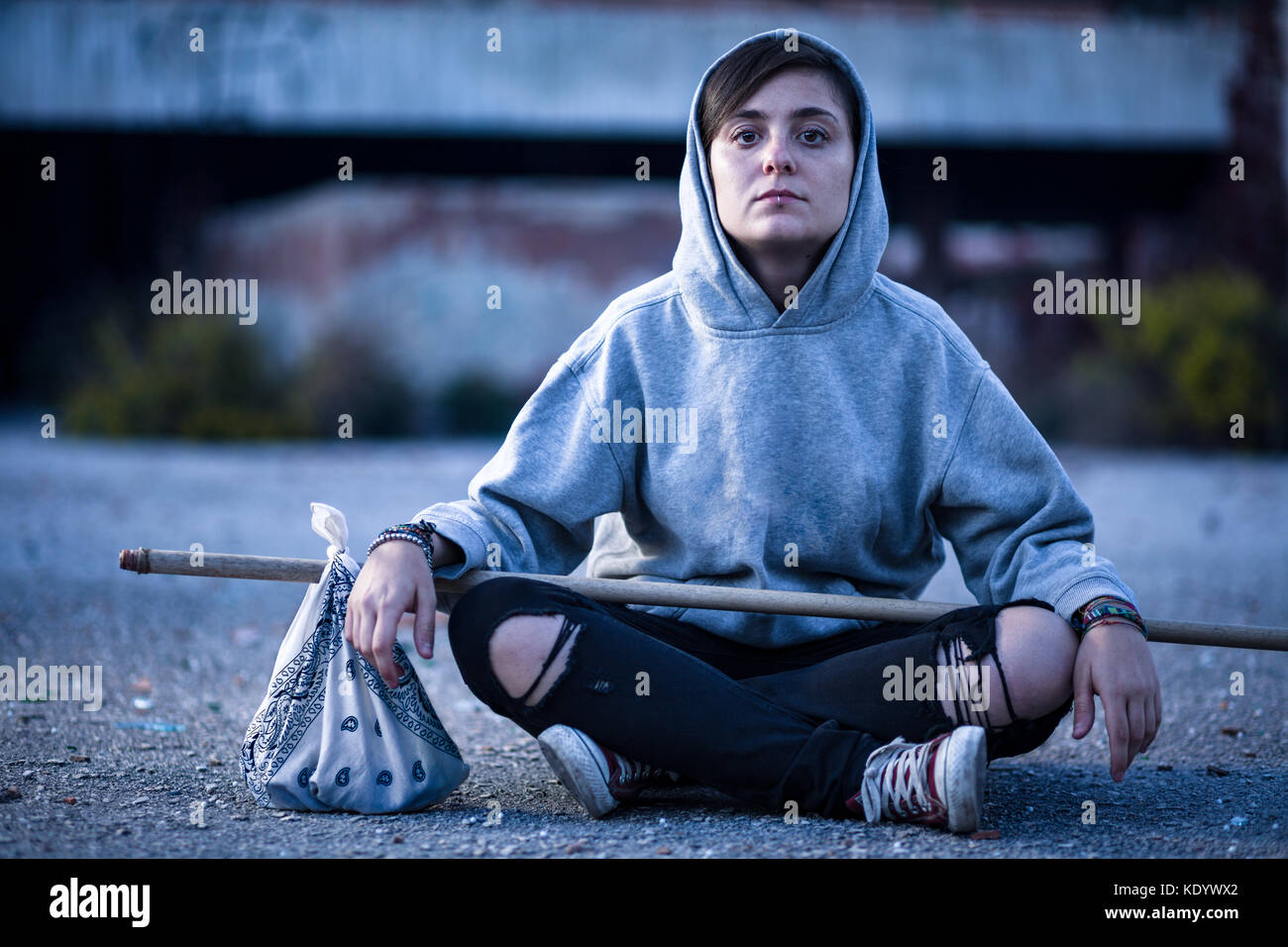 Vagrant Woman with Hobo Stick Sitting on the Street - Stock Image