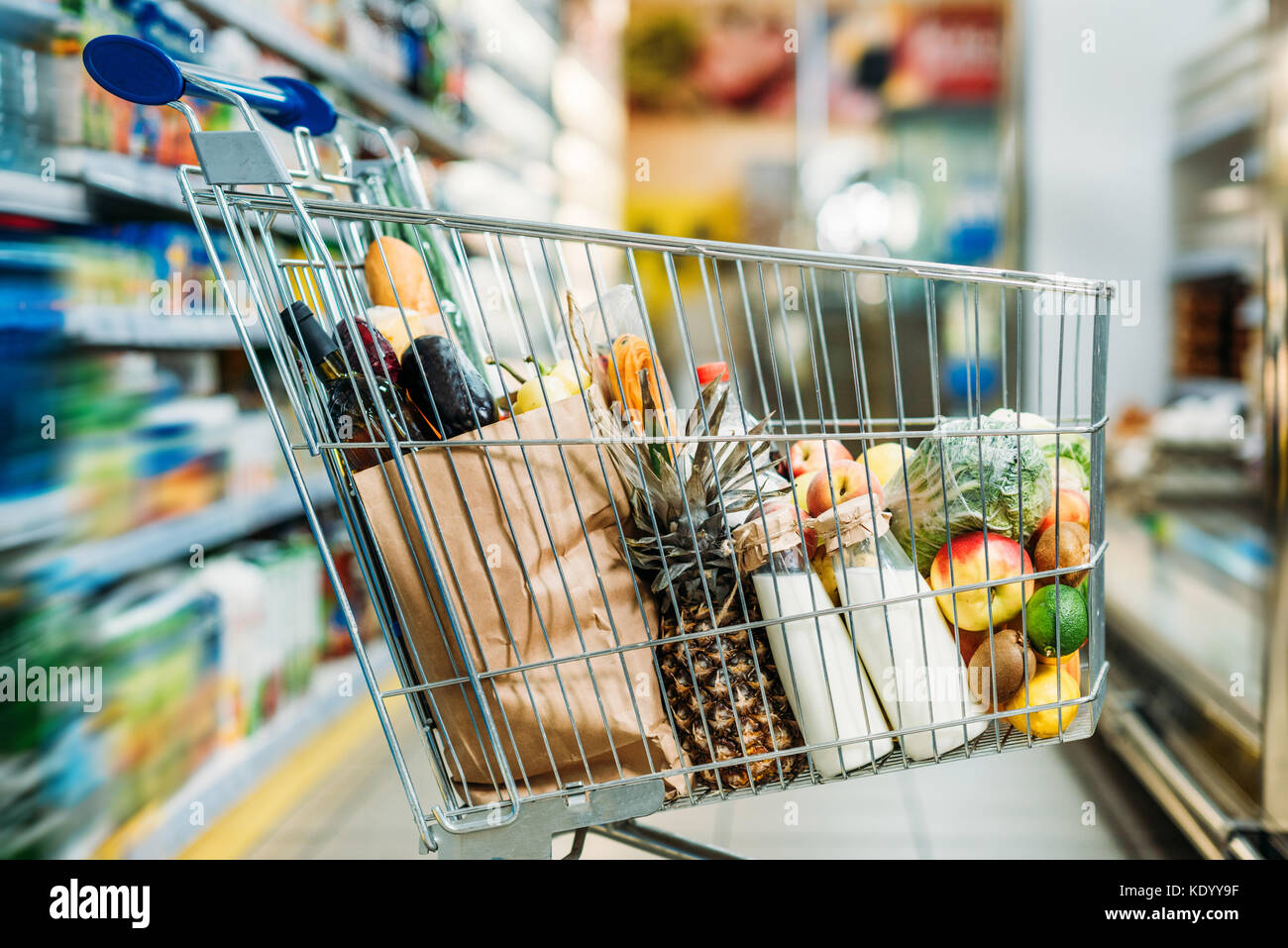 shopping cart with purchases in supermarket - Stock Image