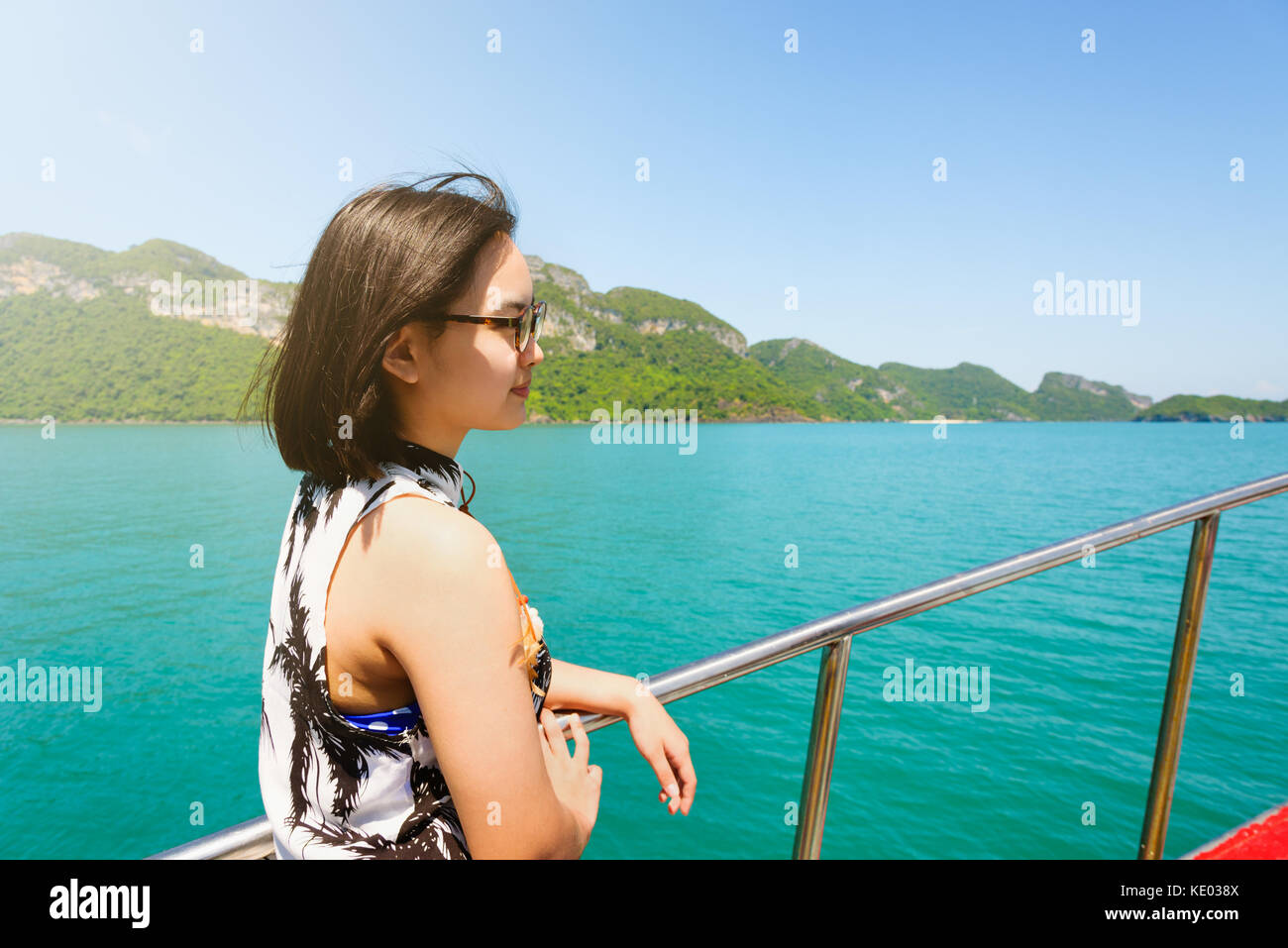 Cute young woman with eyeglasses smiling happily on the boat while cruising the natural of the sea island and under - Stock Image