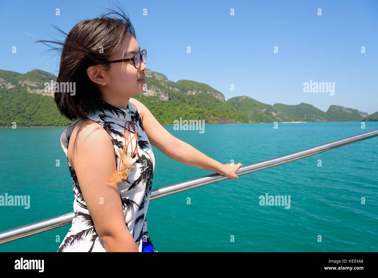 Cute young woman with eyeglasses smiling happily on the boat while cruising the beautiful natural of the blue sea - Stock Image