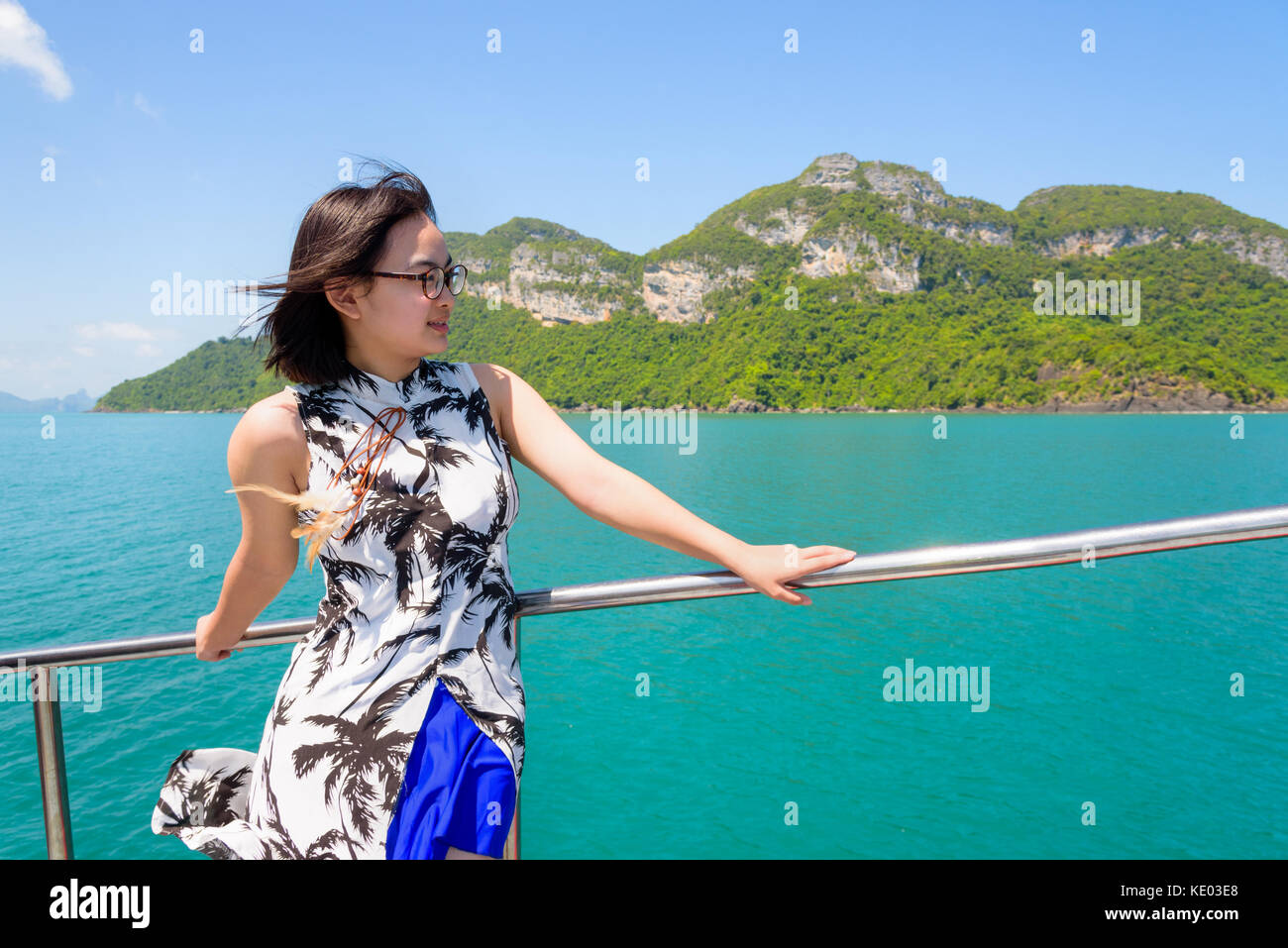 Asian young woman with eyeglasses smiling happily on the boat while cruising the beautiful natural of the blue sea - Stock Image