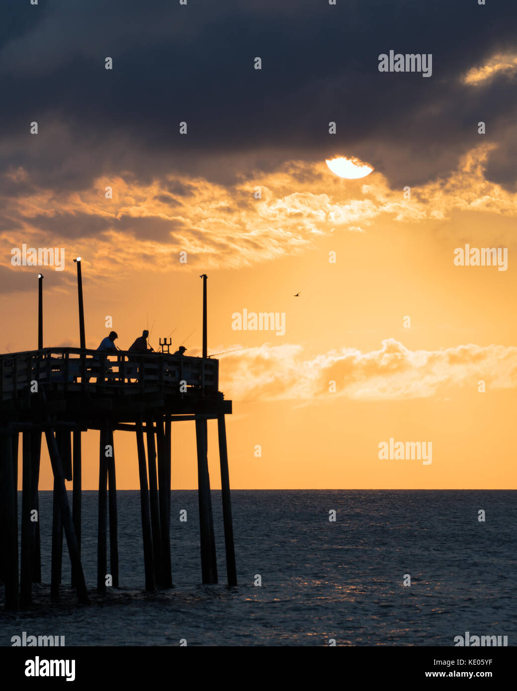 Fisherman try their luck shortly after sunrise at the Avon fishing pier on Hatteras Island, North Carolina. Stock Photo