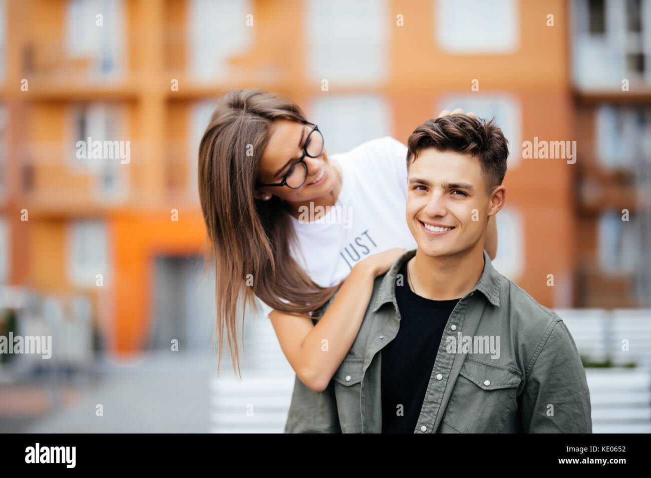 Beautiful young couple in sun glasses looking at each other and smiling while standing outdoors. Girl piggyback - Stock Image
