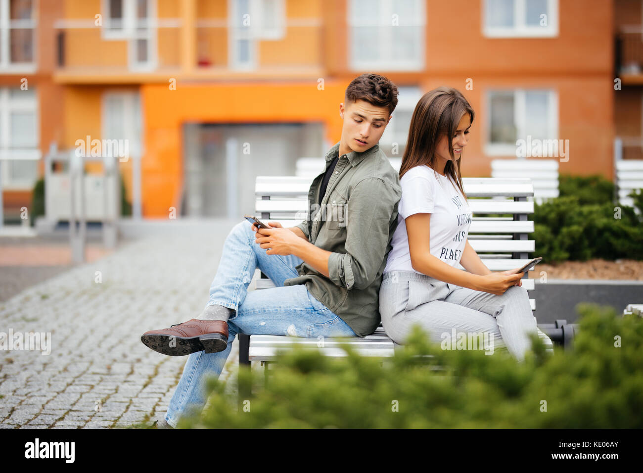 Young Caucasian couple on date, sitting back to back on park bench holding cellphones in hands, using app, making - Stock Image